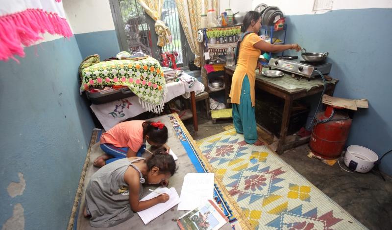 दुई छोरीलाई कोठामा राखेर पढाउँदै मध्यम वर्गीय नेपाली महिला / तस्बिर : गुगल