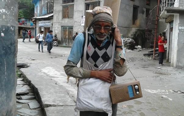 रेडियो बाजेः बझाङको चयनपुर आसपासका क्षेत्रमा भारी बोकेर जीविकोपार्जन गर्ने मदनबहादुर रसाइली । जतिसुकै ठूलो भारी भए पनि साथमा रेडियो बोक्न नछुटाउने भएका कारण स्थानीयबासी उहाँलाई 'रेडियो बाजे' का रुपमा चिन्छन् । तस्विरः लिलप्रकाश चन्द